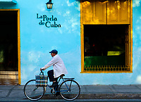 CAMAGUEY, CUBA - CIRCA JANUARY 2020: Man riding a bicycle in the streets of Camaguey