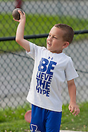 Middletown, New York - A young boy throws the shot during the Twilight Track and Field Series run by the Middletown High School Varsity track program on July 22, 2014.