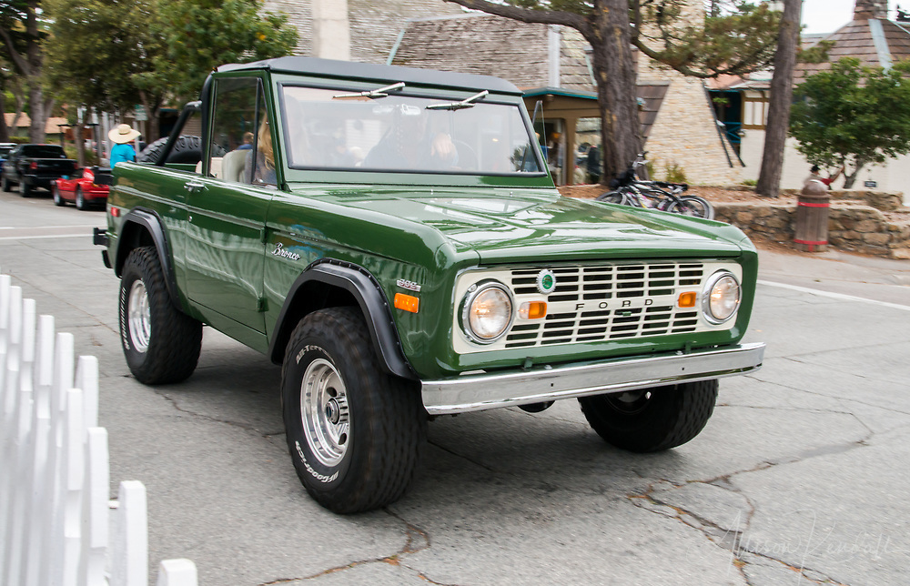 A vintage green Ford Bronco drives past the 2017 Carmel-by-the-Sea Concours on the Avenue