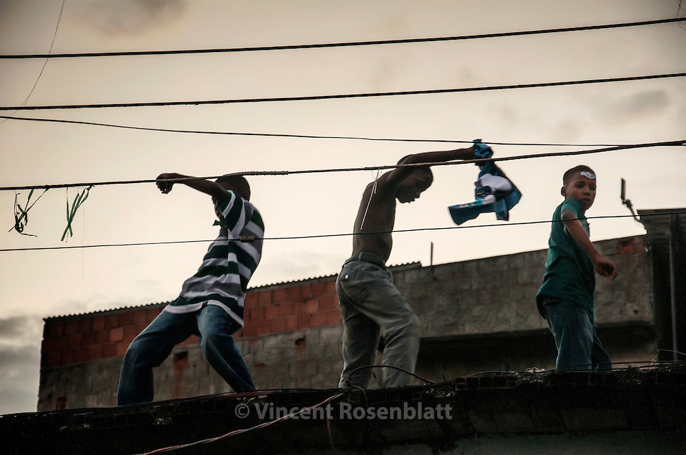 Kids ancing on the roof at end of the baile Funk in the favela of São João, early morning in the zona norte of Rio de Janeiro.