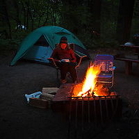 A middle aged woman sitting reading a book next to a camp fire.