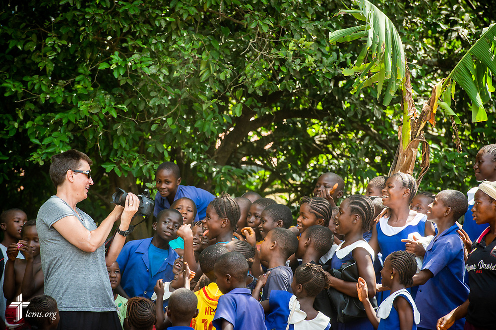 Debra Freese, area communications director for West Africa, shares photographs with schoolchildren on the first day of the LCMS Mercy Medical Team on Monday, May 7, 2018, in the Yardu village outside Koidu, Sierra Leone, West Africa. LCMS Communications/Erik M. Lunsford