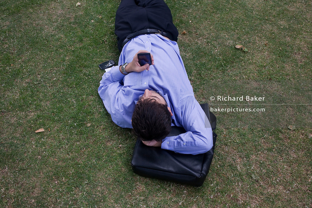 Young businessman fiddles with his touch pad phone during a lunchtime break on the grass in St. Paul's cathedral churchyard.