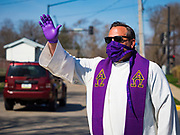 """05 APRIL 2020 - DES MOINES, IOWA:  Rev. RUSSELL LACKEY blesses people in the neighborhood around Grand View University after a drive through Palm Sunday service sponsored by Luther Memorial Church on the campus of Grand View University in Des Moines. About 150 people attended the service. They remained in their cars while the ministers read a short passage from the Bible, handed out palms and blessed them. On Sunday, 05 April, Iowa reported 868 confirmed cases of the Novel Coronavirus (SARS-CoV-2) and COVID-19. There have been 22 deaths attributed to COVID-19 in Iowa. Restaurants, bars, movie theaters, places that draw crowds are closed until 30 April. The Governor has not ordered """"shelter in place"""" but several Mayors, including the Mayor of Des Moines, have asked residents to stay in their homes for all but essential needs. People are being encouraged to practice """"social distancing"""" and many businesses are requiring or encouraging employees to telecommute.       PHOTO BY JACK KURTZ"""