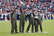 Members of the U.S. military, one of whom sports a Tennessee Titans jersey under his military uniform, wave to fans as they are introduced after a pregame jet flyover during the Tennessee Titans 2016 NFL week 14 regular season football game against the Denver Broncos on Sunday, Dec. 11, 2016 in Nashville, Tenn. The Titans won the game 13-10. (©Paul Anthony Spinelli)