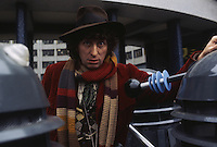 English actor Tom Baker in his role as the fourth incarnation of Doctor Who in the British science fiction television series of the same name, circa 1975. With him are two of his arch-enemies the Daleks.