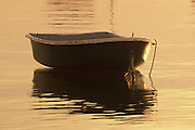 USA, Newport, RI - Dinghy floats by the the Clingstone house on the rock, golden sunrise.