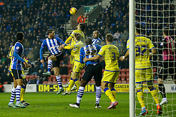 Chris McCann of Wigan and Atdhe Nuhiu of Sheffield Wednesday compete in the air at a corner - Photo mandatory by-line: Rogan Thomson/JMP - 07966 386802 - 30/12/2014 - SPORT - FOOTBALL - Wigan, England - DW Stadium - Wigan Athletic v Sheffield Wednesday - Sky Bet Championship.