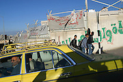 A taxi passes a security wall in Nablus, West Bank.