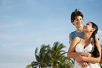 Teenage couple (16-17) embracing on beach