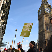 London,UK, 24th January 2015 :  Occupy London have organised a mass protest demanding that the government scrap Trident after the 2015 general election. Demonstrators hold placards that read: 'jobs not trident' to send a clear message to MPs: Trident must be scrapped, not replaced outside the House of Parliament in London. Photo by See Li