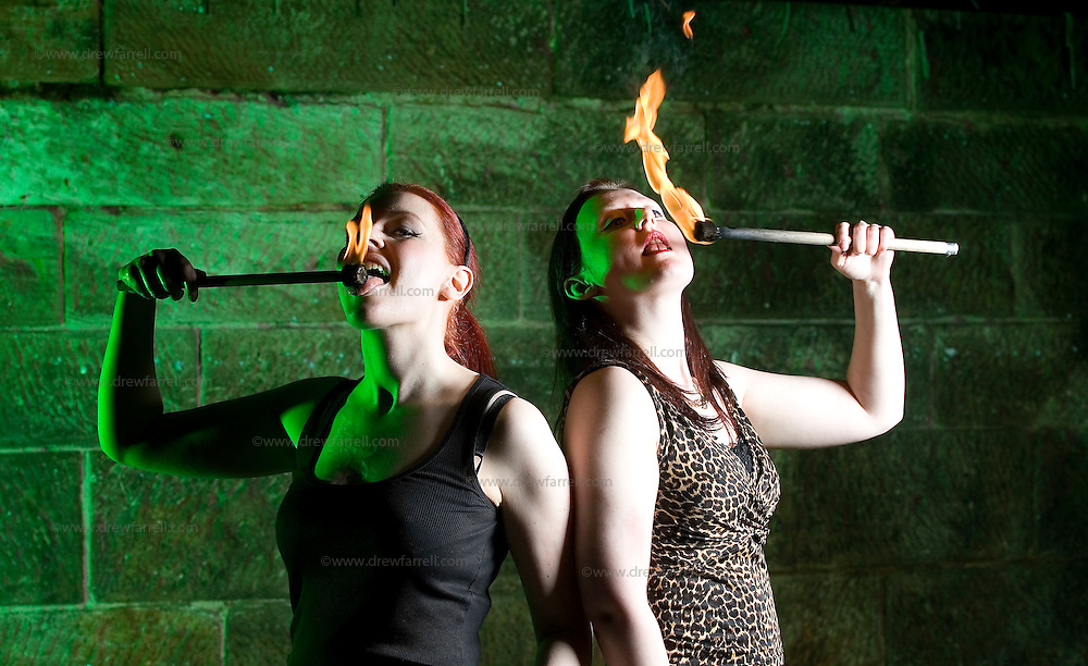 Picture shows :  Ailsa Longmuir  (in black)  and fire performer Lucille Burn (animal print)..Writer Ailsa Longmuir  (in black) learns the Art of Fire Breathing / Fire Eating with her first  lesson from the Purple Productions team of Rufus T. Fahrenheit and Lucille Burn (animal print)....Picture Drew Farrell Tel : 07721-735041.