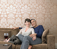 Smiling couple relaxing on sofa in living room (portrait)
