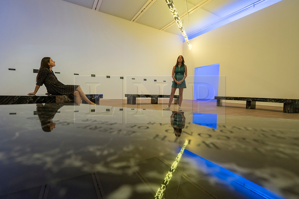 """© Licensed to London News Pictures. 20/07/2018. LONDON, UK. Staff members view """"FLOOR 2015"""", a large scale kaleidoscopic work, by Jenny Holzer at the preview of ARTIST ROOMS: Jenny Holzer at Tate Modern. The annual free display includes text-based installations and paintings by the American artist Jenny Holzer and runs 23 July to summer 2019.  Photo credit: Stephen Chung/LNP"""
