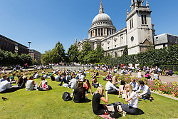 © Licensed to London News Pictures. 03/04/2014. London, UK. Crowds of office workers and tourists enjoy the sunshine near St Paul's Cathedral in London at lunchtime on 3 July 2014. Photo credit : Vickie Flores/LNP