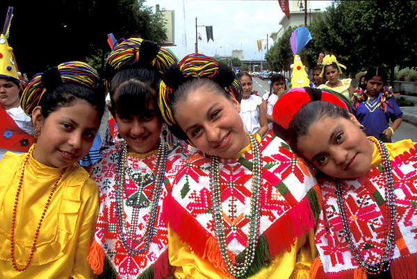 Stock photo of four young girls dressed in typical Mexican costumes for the Cinco de Mayo parade in downtown Houston Texas