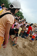A sandcastle artist demonstrating on how to build a sandcastle on the beach at East Coast Park, Singapore