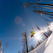 Forrest Jillson grabs an air amongst the wildfire burned trees in the Teton backcountry.