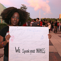 "Shani Angela holds a sign of victims names that were previously brutalized or harassed by the police, during the ""National Moment of Silence"" event at the Lake Eola bandshell in downtown Orlando, Florida on Thursday, August 14, 2014. In light of the recent killing of eighteen year old Mike Brown in Ferguson, Missouri, citizens across America are gathering in solidarity to hold vigils and observe a moment of silence to honor victims of suspected police brutality. (AP Photo/Alex Menendez)"