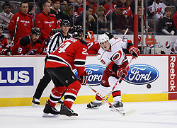 Oct 17, 2009; Newark, NJ, USA; Carolina Hurricanes right wing Tim Conboy (38) flips the puck past New Jersey Devils defenseman Bryce Salvador (24) during the first period at the Prudential Center.