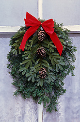 North America, USA, Washington, Leavenworth. Christmas wreath on white window
