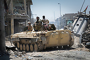 Soldiers of the Iraqi Army ride on a tank towards the frontline in the Old City of Mosul. Although victory over Islamic State has been declared in Mosul, fighting and IS counter-attacks continue.