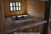"A bed and torture devices used by the Khmer Rouge to interrogate prisoners during the Pol Pot regime are depicted in Building ""A"" at Tuol Sleng Genocide Museum in Phnom Penh, Cambodia. Building ""A"" contains three stories divided into 20 cells.  The first story has 10 cells used for jailing, interrogating, and torturing the prisoners who had been high officials. The second and third floors have 5 big cells each used for the same purpose."