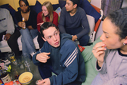 Multiracial group of teenage boys and girls sitting together drinking alcohol; eating snacks and chatting,