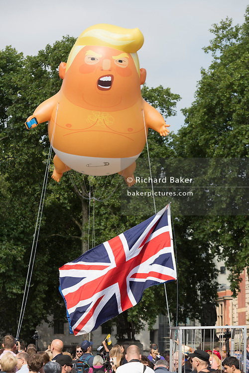 London, UK: The inflatable balloon called Baby Trump flies above Parliament Square in Westminster, the seat of the UK Parliament, during the US President's visit to the UK, on 13th July 2018, in London, England. Baby Trump is a 20ft high orange blimp depicting the US President as an enraged, smartphone-clutching infant - and given special permission to appear above the capital by London Mayor Sadiq Khan because of its protest rather than artistic nature. It is the brainchild of Graphic designer Matt Bonner. Photo by Richard Baker / Alamy Live News