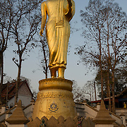 Sun rise at Wat Phra That Khao Noi. It offers a great view over Nan and the surrounding valleys from about 800 feet. Besides the Ubosot with a white Buddha image and the small chedi is a more modern platform with a walking Buddha image, which overlooks the valley.