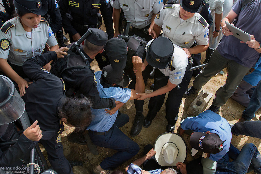 Police officers begin to arrest locals in peaceful protest at the La Puya camp only meters away from the entrance to the El Tambor mine. After two years and two months of peacefully blocking the entrance to U.S.-based Kappes, Cassiday & Associates (KCA) El Tambor gold mine, local residents of San Jose del Golfo and San Pedro Ayampuc were violently evicted by Guatemalan Police forces in order to introduce heavy machinery inside the industrial site. La Puya, San Pedro Ayampuc, Guatemala. May 23, 2014.