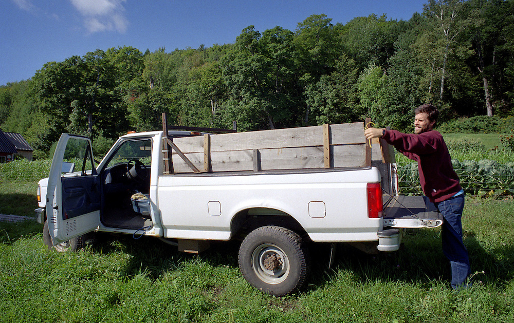 Chuck Wooster of Hartford, Vt., puts up wooden sides on his pickup bed for transporting his sheep at Sunrise Farm in White River Junction, Vt., on Sept. 2, 2004. (Photo by Geoff Hansen)