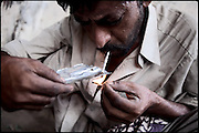 "Safir Alì, 28 years old, homeless and heroin addict, smokes his dose of white powder. Usually the druggies consume the substances three time per day and the effects remains for about 5 hours. Rawalpindi, Pakistan, on friday, August 29 2008.....""Pakistan is one of the countries hardest hits by the narcotics abuse into the world, during the last years it is facing a dramatic crisis as it regards the heroin consumption. The Unodc (United Nations Office on Drugs and Crime) has reported a conspicuous decline in heroin production in Southeast Asia, while damage to a big expansion in Southwest Asia. Pakistan falls under the Golden Crescent, which is one of the two major illicit opium producing centres in Asia, situated in the mountain area at the borderline between Iran, Afghanistan and Pakistan itself. .During the last 20 years drug trafficking is flourishing in the Country. It is the key transit point for Afghan drugs, including heroin, opium, morphine, and hashish, bound for Western countries, the Arab states of the Persian Gulf and Africa..Hashish and heroin seem to be the preferred drugs prevalence among males in the age bracket of 15-45 years, women comprise only 3%. More then 5% of whole country's population (constituted by around 170 milion individuals),  are regular heroin users, this abuse is conspicuous as more of an urban phenomenon. The substance is usually smoked or the smoke is inhaled, while small number of injection cases have begun to emerge in some few areas..Statistics say, drug addicts have six years of education. Heroin has been identified as the drug predominantly responsible for creating unrest in the society."""