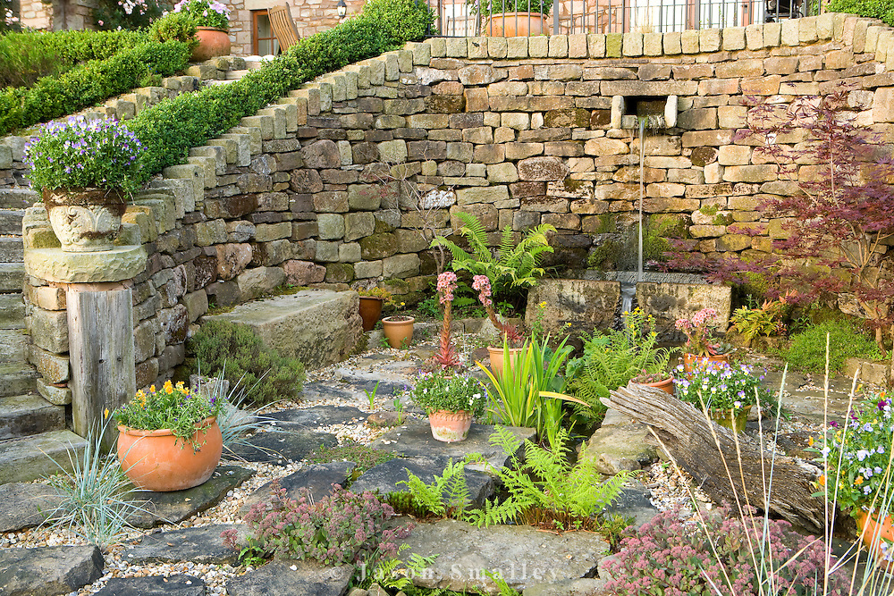 large rockery or patio with ferns and water feature