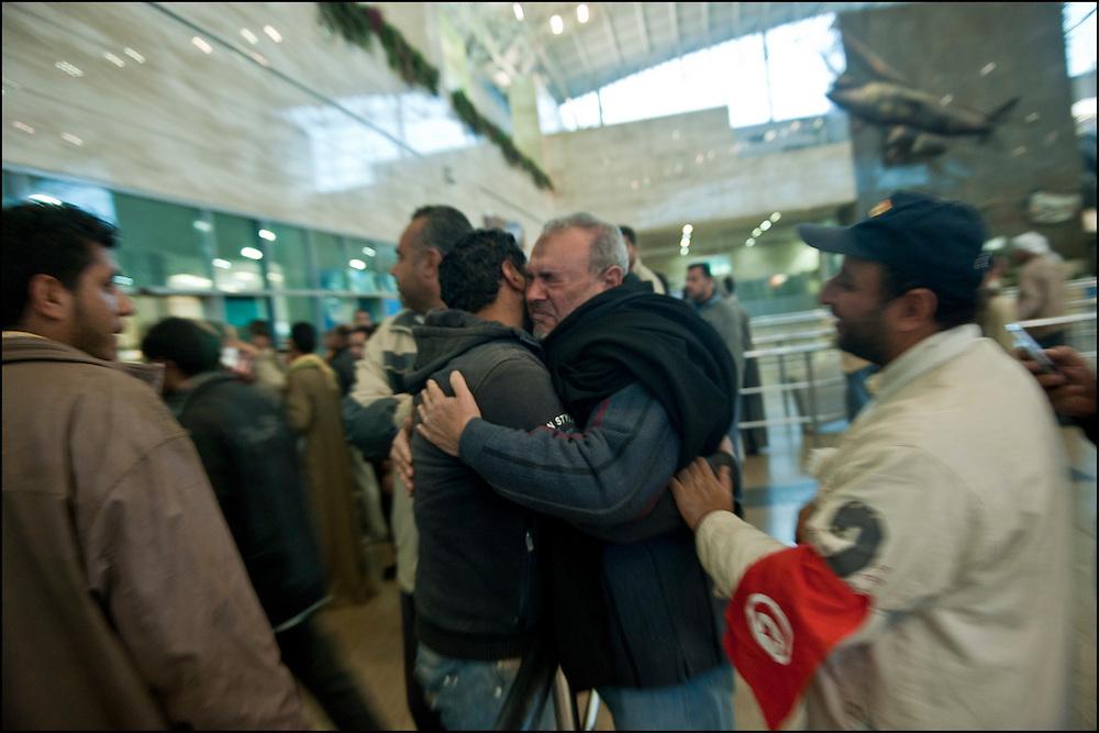 Le père de Mohamad retrouve son fils à l'aéroport du Caire. Cela fait 14 mois que Mohamad est parti travailler en Libye. Mohamad Ahmed El Deb, 33 ans originaire de Tanta en Egypte, ouvrier dans le Batiment en Libye qui a fui vers la Tunisie quand son patron lui a rendu son passeport avant de prendre la fuite vers une destination étrangère. Seule explication laissée:  les mois de Janvier et de Février ne seront pas payés. Dans l'avion qui le ramène au Caire. © Benjamin Girette/IP3 press
