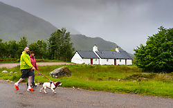 Glen Coe, Scotland, UK. 4 July, 2020. Tourists travel to Glen Coe on first weekend after 5 mile travel restriction was lifted by the Scottish Government. Pictured; Couple walking dog at Blackrock Cottage at Glen Coe ski area. Iain Masterton/Alamy Live News