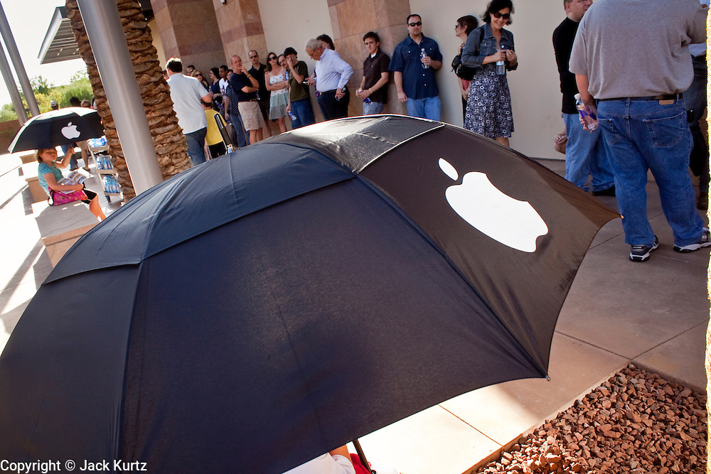 12 JUNE 2009 -- SCOTTSDALE, AZ: People hold umbrellas with the Apple logo on them for shade from the sun during the grand opening of the new Apple Store in Scottsdale, AZ. The outlet will be Arizona's largest Apple Store, occupying nearly 10,000 square feet in the Outdoor Lifestyle Center in the Scottsdale Quarter. The store, the fifth in the Phoenix area, uses a radically different design from other Apple Stores in some respects. Ceilings in the building are approximately 20 feet high, and lined with a 75-foot long skylight, reducing dependence on artificial lighting. Aiding the skylight is an all-glass front and rear, permitting visitors to see directly through the store. More than one thousand people lined to get into the store during the grand opening. Photo by Jack Kurtz