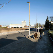 "Nederland Utrecht 31 januari 2009 20090131 Foto: David Rozing ..Serie vogelaarwijk Kanaleneiland .Reportage documentary on deprived area / projects "" Kanaleneiland "" This area is on a list with projects which need help of the government because of degradation in the area etc..Vrouw laat hond uit naast braakliigend stuk terrein op Kanaleneiland zuid.Woman walking the dog near empty derelict location ..project, suburb, suburbian, problem. Neighboorhood, neighboorhoods, district, city, problems, daily lifeFoto: David Rozing"