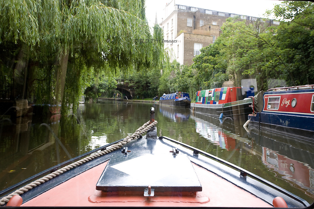 Being there: on a barge moving down the Regent's Canal; other barges used as houseboats docked along the canal's edge.  Willow trees and other deciduous trees hang over the canal.