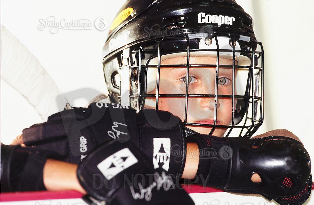 2 June 1996:  Young kid wearing Cooper helmet with cage and Easton Wayne Gretzky gloves watches a roller hockey game at the Gretzky Center in Irvine, CA.