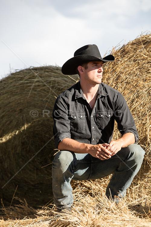 cowboy squatting down next to hay bales