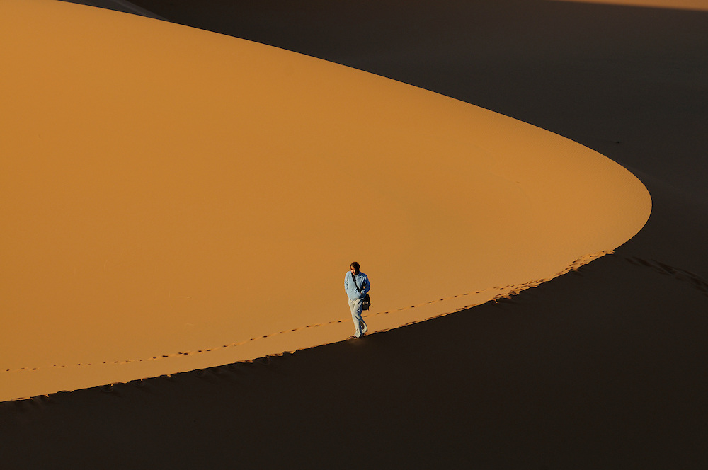 A woman is walking on the top of a dune in a sand desert. Merzouga. Morocco. Africa.