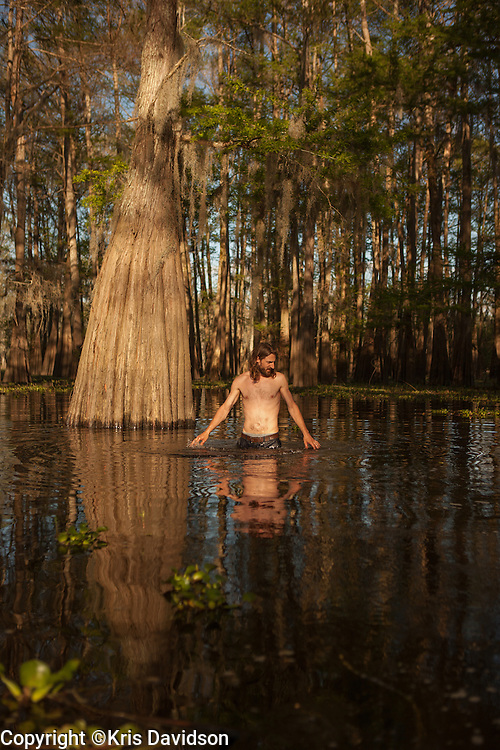 "Cypress tree ""salvage pirate"" and furniture builder, Hamilton Hall, searches for old cypress logs in the Atchafalaya Basin by feeling the swamp floor with his feet. Hall finds and recovers cypress woods from logging days and builds furniture with the logs. It is illegal to cut down cypress trees now -- so the wood, found by scavengers such as Hall, is a rare commodity."