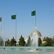 Fountains and flags of Turkmenistan in front of the Turkmenbashi Ruhy Mosque or Gypjak Mosque, with the former president's tomb in the background