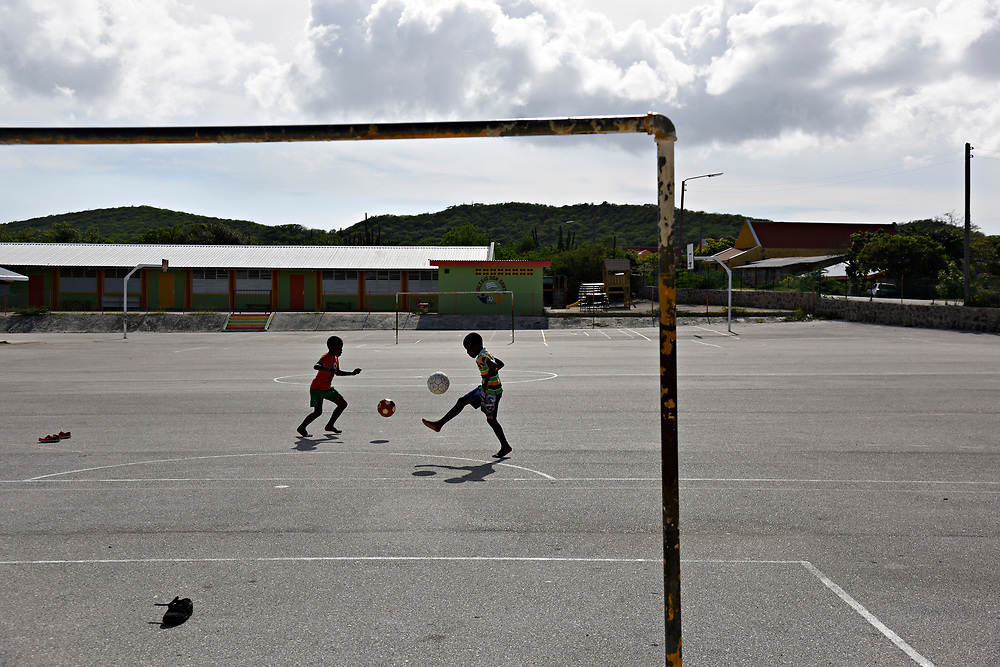 WILLEMSTAD, CURACAO - DECEMBER 12, 2014: Youngsters play soccer in the schoolyard at the Kolegio Don Sarto in the town of Soto. In Curacao, baseball is second in popularity to a country crazy about soccer. (photo by Melissa Lyttle)