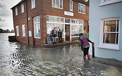 © Licensed to London News Pictures. 01/10/2019. Bosham, UK. A woman wades through seawater as the high tide covers roads in the village of Bosham in West Sussex. Parts of the South are being affected by the aftermath of Hurricane Lorenzo with numerous flood warnings in place. Photo credit: Peter Macdiarmid/LNP