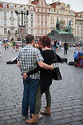 A couple is watching a street musician at Old Town Square in Prague.
