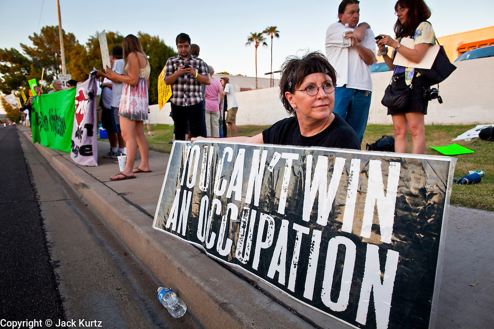 26 SEPTEMBER 2010 - PHOENIX, AZ: Lisa Blank, from Phoenix, sits on the sidewalk during a demonstration against Sen. John McCain Sunday. About 200 people demonstrated and picketed against Arizona Republican Senator John McCain at the studios of KTVK TV in Phoenix, Sunday, Sept 26. They picketed the TV station because McCain was debating his opponents there. They were demonstrating against McCain's positions on the war in Afghanistan, Don't Ask Don't Tell (Gays in the military) and the DREAM Act (for immigrant rights). PHOTO BY JACK KURTZ