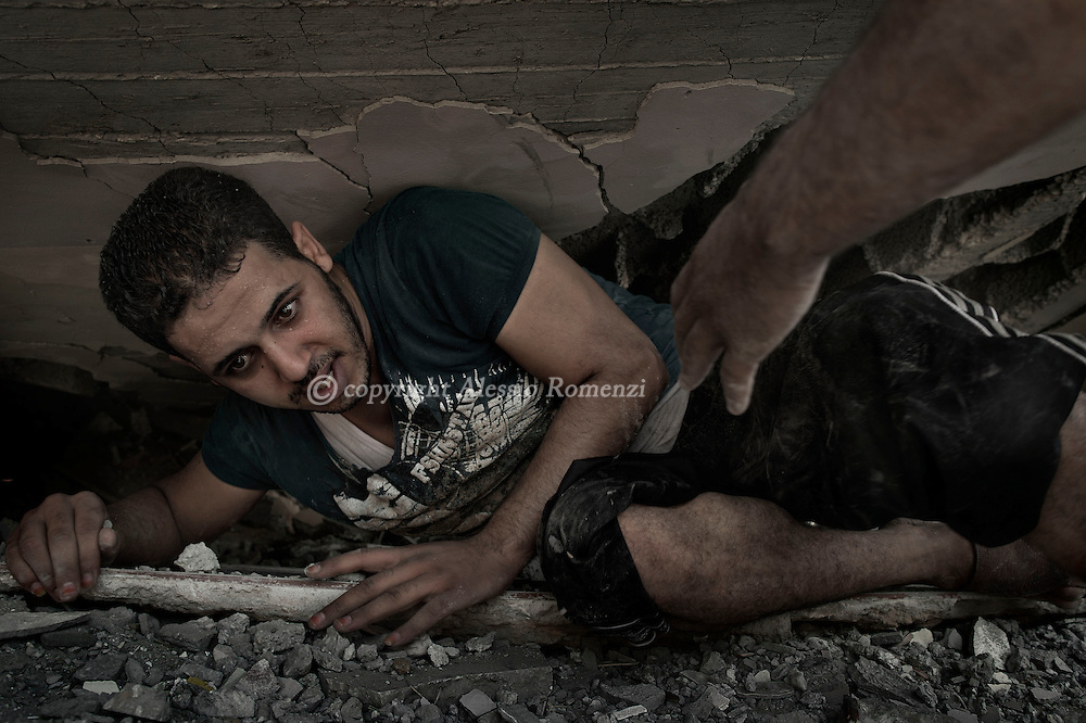 Gaza Strip, Shati refugee camp: A Palestinian comes out of the rubble after he crawled inside looking for survivors.<br /> The house located in Shati refugee camp was destroyed by an Israeli airstrike on August 4, 2012. ALESSIO ROMENZI