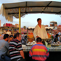 Food Stall at Jemaa el Fna in Marrakech, Morocco<br /> The food stalls at Jemaa el Fna are a great way to sample Moroccan cuisine from the bland to the bizarre. These men are waiting for a bowl of couscous. This popular dish consists of small, steamed pellets of flour (semolina) topped with a stew of vegetables and meat. Other food vendors serve lamb, pastille (meat pie) and seafood. In the background is a cart filled with fresh Moroccan oranges waiting to be squeezed into juice.  One merchant proudly displayed lamb heads. Although Lahem Ras is considered a delicacy, the charred skull with bulging eyes looks less than appetizing.